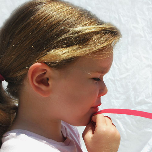 Kind, das über Papierstreifen pustet - Physik Experiment zum Bernoulli-Effekt